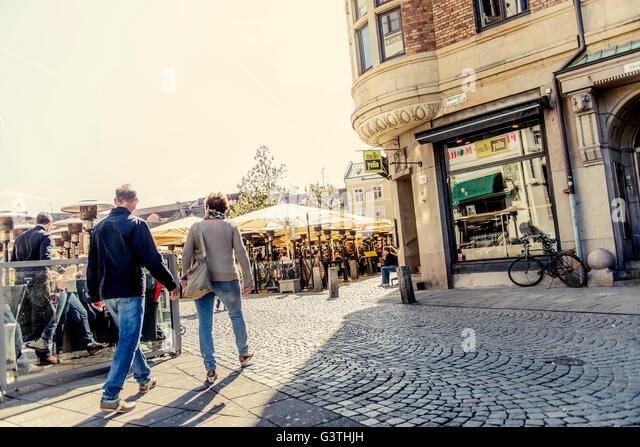 Sweden, Skane, Malmo, Lilla torg, Senior couple holding handsi n town square - Stock Image