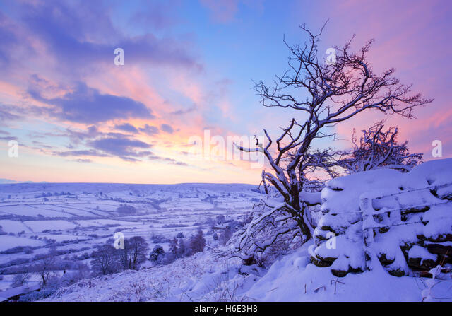 Colourful daybreak pre sunrise view of Danby Dale in North York Moors national park during winter with snow on the - Stock Image