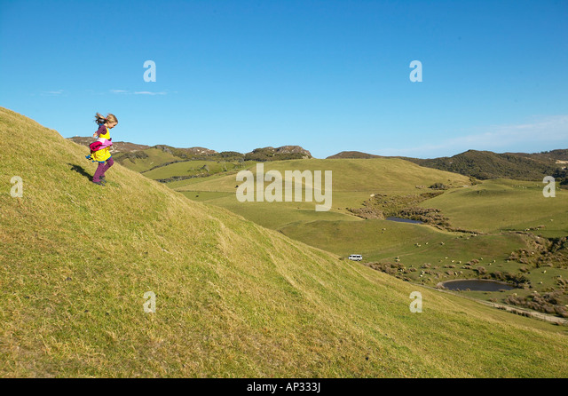 Girl running on farmland, grazing sheep, near Puponga, Golden Bay, northern coast of South Island, New Zealand - Stock Image