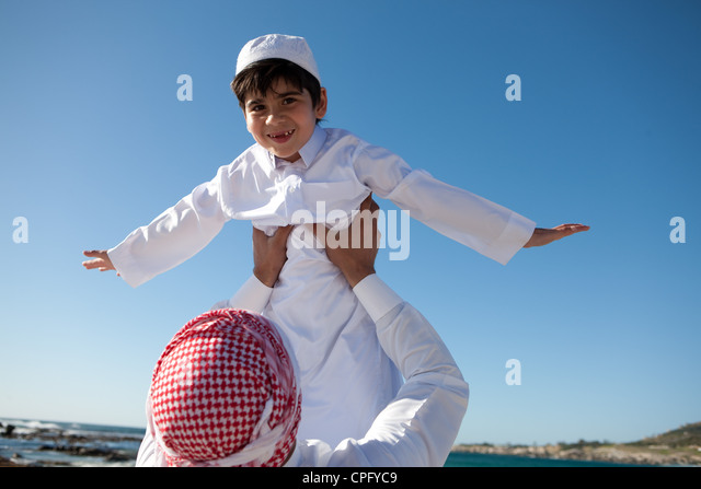 Portrait of arab father lifting his son on beach, boy arms raised. - Stock-Bilder