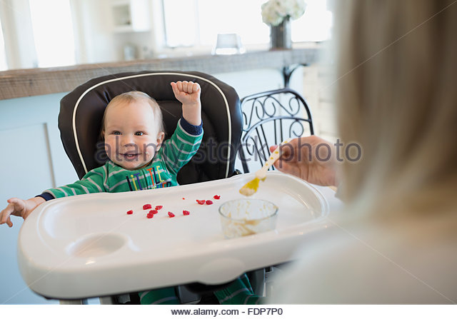 Mother feeding enthusiastic baby boy in high chair - Stock Image