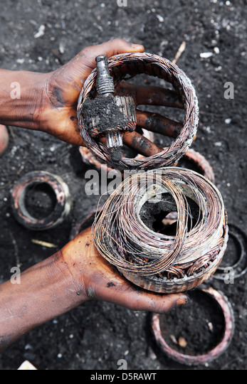 By fire exposed copper windings from a electronics. Agbogbloshie burning site for e-waste and used computers in - Stock Image