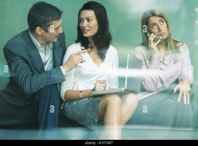 Three businesspeople using laptop and cell phone - Stock Image