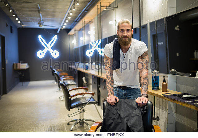 Portrait confident hipster hairstylist in hair salon - Stock-Bilder