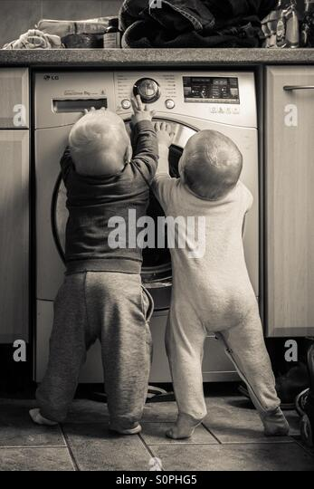 Twin boys playing with the washing machine - Stock-Bilder