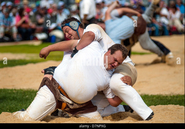 Schwingen (Swiss wrestling) at folklore festival, with spectators in background - Stock Image