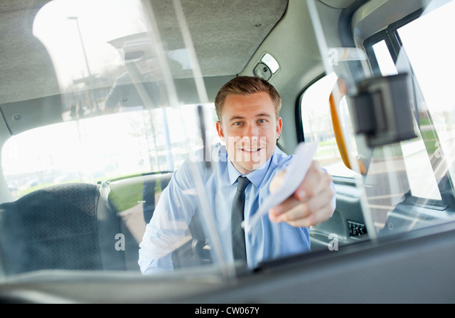 Businessman paying taxi driver - Stock Image