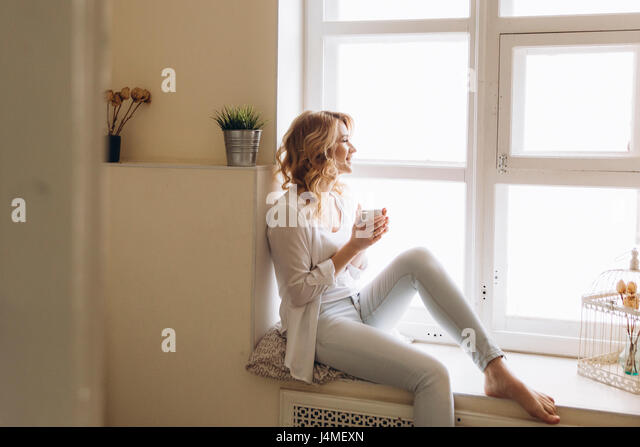 Middle Eastern woman sitting in window sill drinking coffee - Stock-Bilder