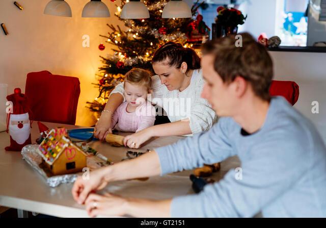 Family preparing gingerbread cookies at home - Stock-Bilder
