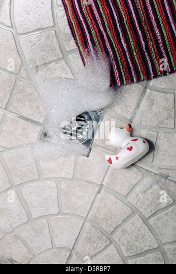 a rubber duck with foam sitting in a shower - Stock Image