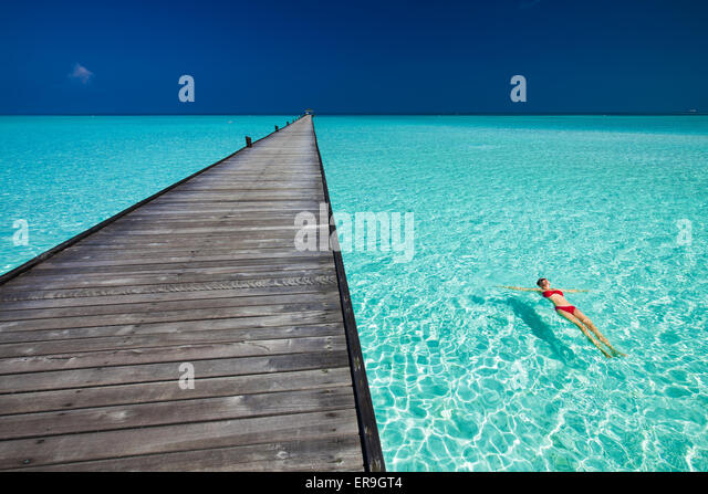 Young woman in red bikini swimming next to jetty in azure water of Maldives - Stock-Bilder