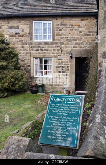 Plague Cottage sign and house, Eyam, Derbyshire, England, UK - Stock Image