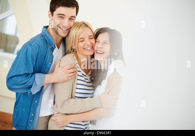 Portrait of joyful family of three at home - Stock Image