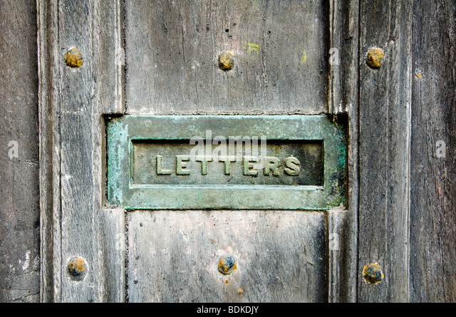 A letter box, with a verdigris patina, inset into an old and weathered oak door, with heavy nails. - Stock Image