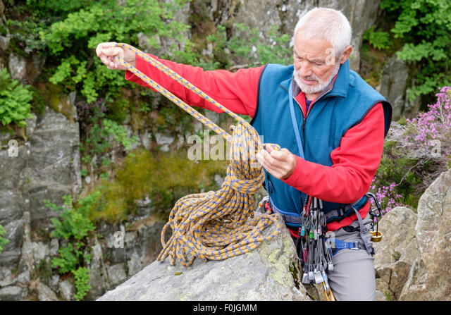 Experienced active elderly senior rock climber unwrapping a climbing rope at top of a crag climb. Snowdonia, North - Stock Image