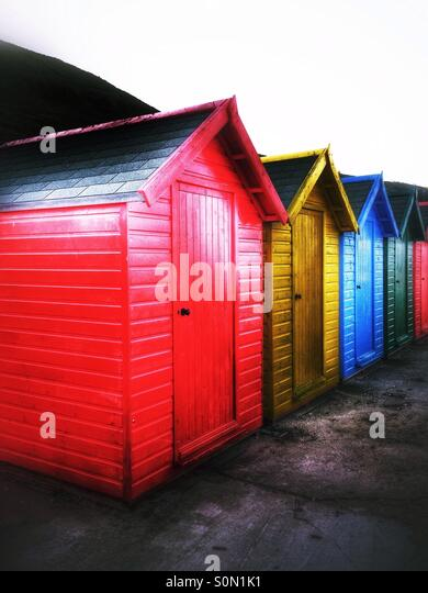 Colourfully painted beach huts at Whitby - Stock Image