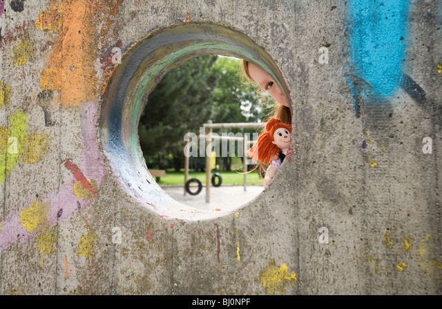 young girl peeking through hole in wall on playground - Stock Image