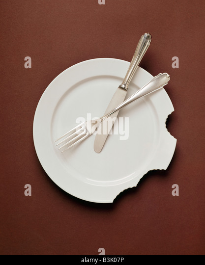 FORK AND KNIFE ON WHITE PLATE WITH HUMAN BITES - Stock-Bilder
