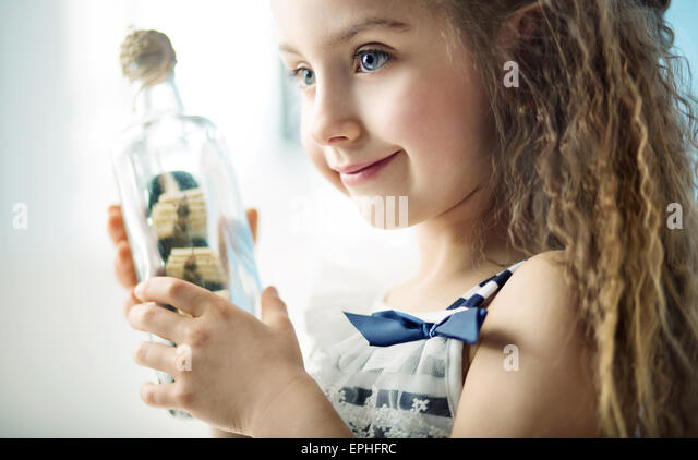 Little kid holding a bottle with a ship - Stock Image