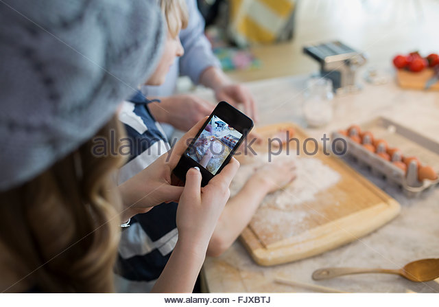 Sister photographing brother baking with cell phone - Stock Image