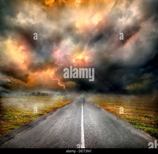 Storm clouds and lightning over highway in the field - Stock Image