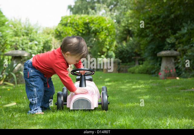 Toddler girl playing with go kart - Stock-Bilder