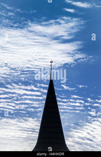 Silhouette of church steeple against Cirrus clouds - France. - Stock Image