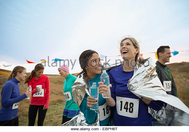 Smiling runners drinking water after marathon - Stock Image