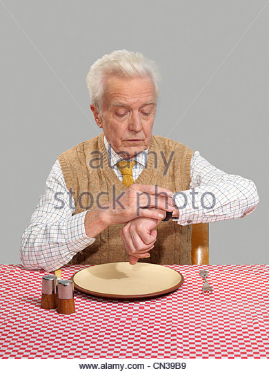 Senior man looking at watch whilst waiting for food - Stock Image