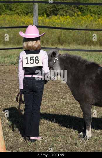 Young girl with pink boots and cowboy hat competing in a horse show halter class with a fuzzy gray miniature horse.. - Stock Image