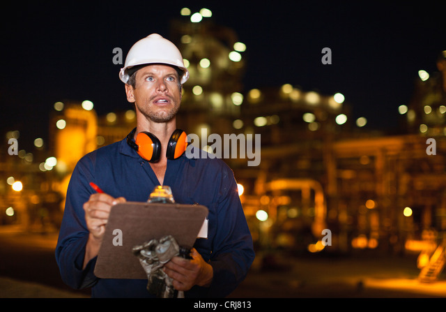 Worker with clipboard at oil refinery - Stock Image