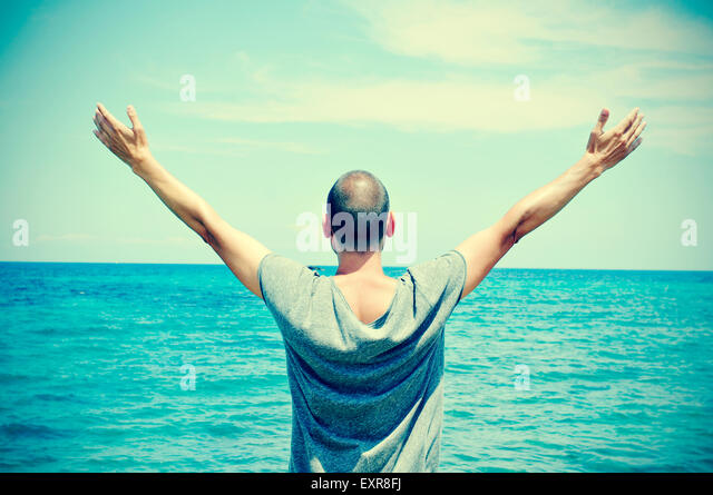 closeup of a young caucasian man seen from behind with his arms in the air in front of the ocean, feeling free, - Stock Image