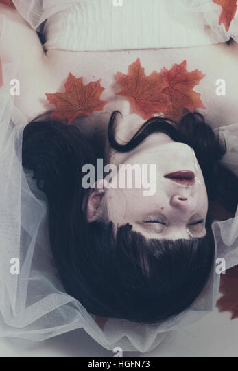 Young brunette woman lying on water with a white dress and red maple leaves - Stock Image