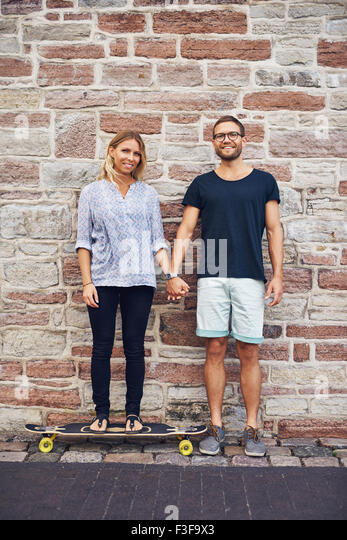 Young couple holding hand leaning against wall - Stock-Bilder