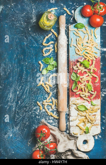 Fresh pasta casarecce, tomatoes, basil, olive oil on colorful board - Stock Image