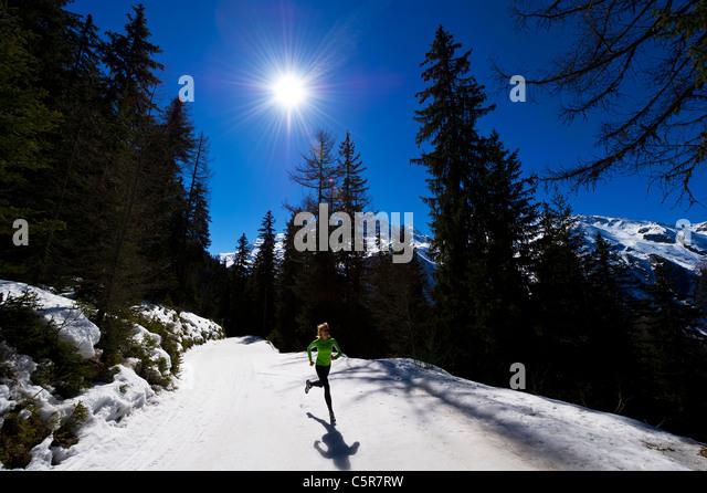 A jogger running on snowy mountains. - Stock-Bilder