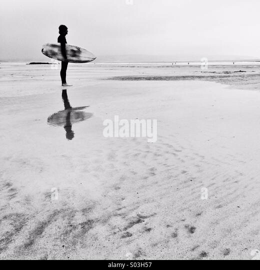 Surfer checking the waves in winter at first light. - Stock Image