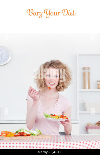 Vary your diet against pretty blonde woman eating some vegetables in the kitchen - Stock-Bilder