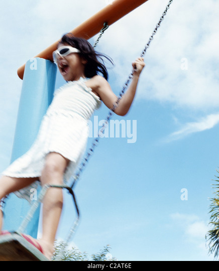 Girl playing on swing, low angle view - Stock Image