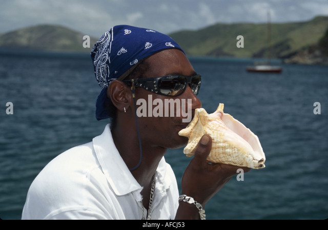 West Indies St. Kitts Black male Spirit of St. Kitts boat captain signals snorkelers conch shell horn - Stock Image