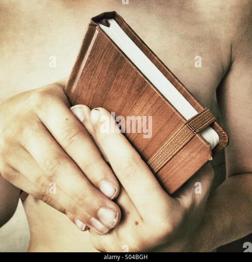 Holding a book tightly - Stock Image