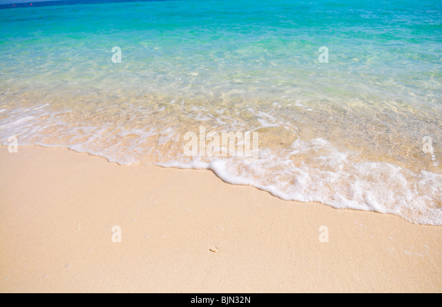 Tropical beach with white coral sand and calm wave - Stock-Bilder