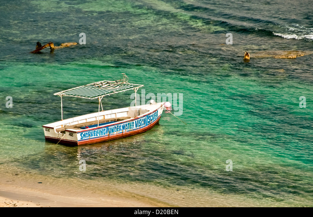Old colorful glass bottom tour boat anchored just offshore, awaiting tourists, Ocho Rios Jamaica - Stock Image