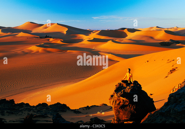 Algeria, Djanet. Sand dunes and rocks. Woman meditating. Sahara Desert. - Stock Image