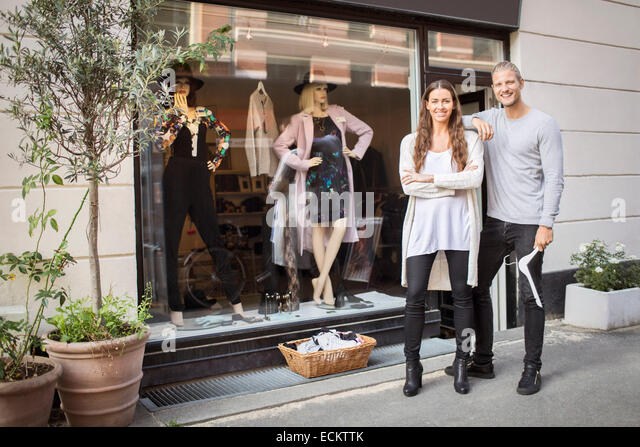 Portrait of smiling owner with female worker standing in front of clothing store - Stock-Bilder