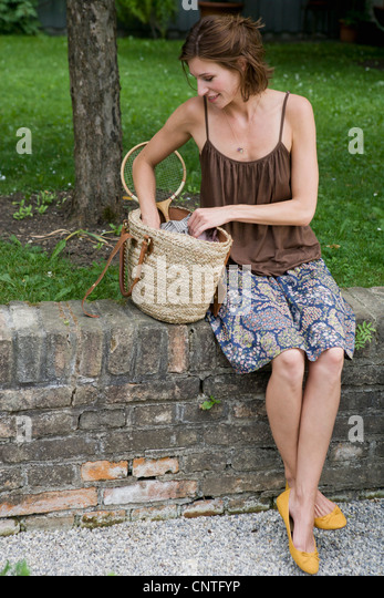 Woman rummaging through purse - Stock Image