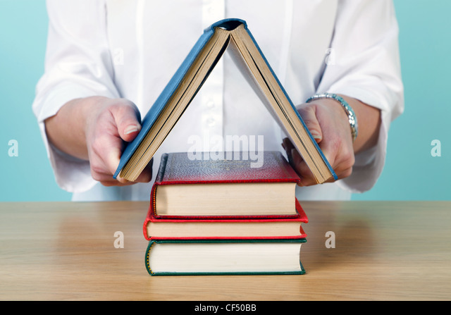 Photo of a woman making a house shape from old hardback books. - Stock Image