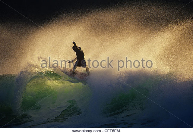 Surfer in early morning pulling a floater, near Tofino, Vancouver Island, British Columbia, Canada. - Stock-Bilder