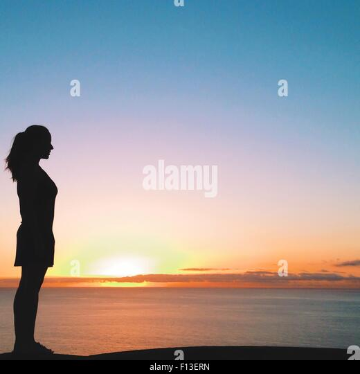 Silhouette of a woman looking out to sea at sunset, Tenerife, Canary Islands, Spain - Stock Image