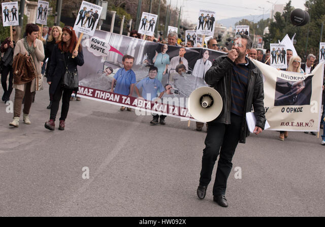 Public healthcare workers march shouting slogans and holding banners and black balloons. Healthcare unionists staged - Stock Image